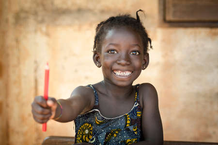 Back To School Symbol - African Girl Toothy Huge Smile Showing Red Pencil. Little African girl holding pen as an educational symbol.