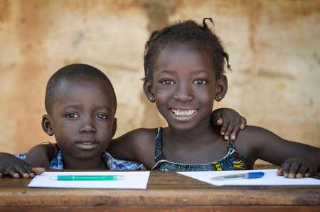 Bildung Symbol: Paare der afrikanischen Kinder in der Schule Lächeln. Zurück zu Schule Symbol - Afrikanische Mädchen Offenes breites Lächeln Zeigen Rot Bleistift Standard-Bild