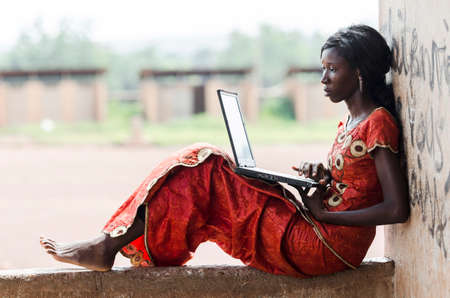 Barefoot African Model Working On Her Laptop Computer Business Symbol Archivio Fotografico