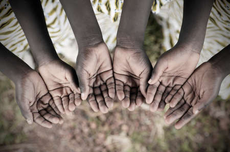 African Children Holding Hands Cupped To Beg Help. Poor African children keeping their cupped hands, asking for help.