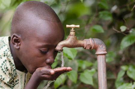 世界シンボルでは水不足。水の懇願するようなアフリカの少年。サハラ以南のアフリカのような場所で水を収集するために時間を失ったし、水上に 写真素材