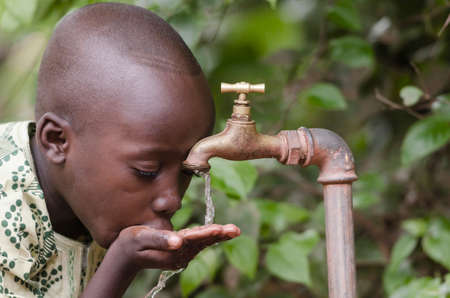 Water scarcity in the world symbol. African boy begging for water. In places like sub-Saharan Africa, time lost to gather water and suffering from water-borne diseases is limiting people's lives. Archivio Fotografico