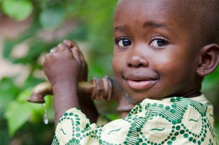Petit garçon noir qui demande de l'eau potable. Sa rareté affecte tous les continents. Environ 1 milliard de personnes vivent dans des zones de pénurie physique et beaucoup d'autres personnes abordent cette situation. Banque d'images - 69936675