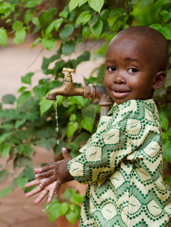 Young African school boy holding hands under a tap. Water scarcity problems concern the inadequate access to safe drinking water. 1 billion people in the developing world don't have access to it. Zdjęcie Seryjne - 69936676