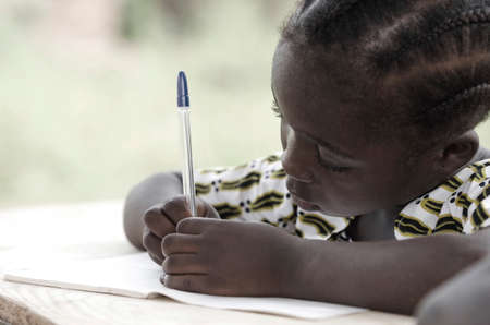 Cute African schoolgirl doing her homework at school: beautiful black girl writing and learning activity with a blue pen. She's sitting in her desk doing her calculating work in her exercise book.