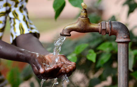 Climate Change Symbol: Handful Of Water Scarsity for Africa Symbol. Hand of an African black boy with water pouring from a tap.