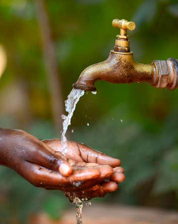 Water Scarsity Symbol - Drinken voor Afrikaanse kinderen. Water Climate Change Symbol: Handvol van waterschaarste for Children Symbol. Holle handen onder een kraan om water te halen voor een Afrikaans meisje. Het is het gebrek aan voldoende beschikbare waterbronnen. Stockfoto