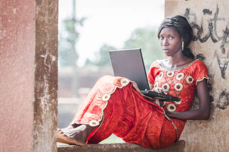 Young girl sitting on stone building and using laptop computer outdoors Stock Photo
