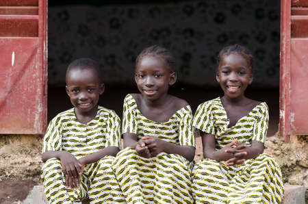 Two young african girls and boy sitting on ground and smiling at camera