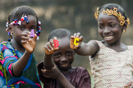 African children holding small colored letters in front of camera