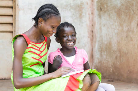 African young woman and girl reading book together outside Stock Photo