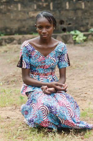 Young african girl sitting on ground and looking at camera
