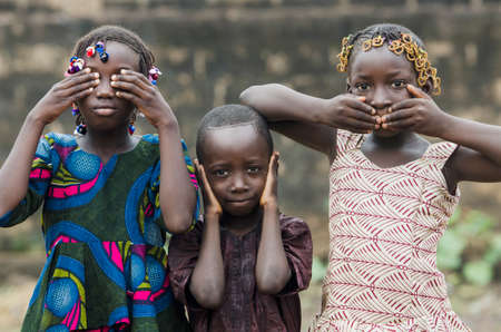 Young african girls and boy posing as famous three wise monkeys Stock Photo