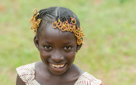 Young african girl with traditional accessories in hair looking at camera Stock Photo