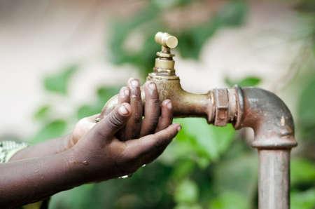 Hands of african child under tap water stream 版權商用圖片