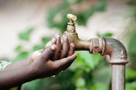 Hands of african child under tap water stream Archivio Fotografico