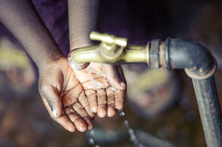 Water pump outdoors with African child with hands cupped