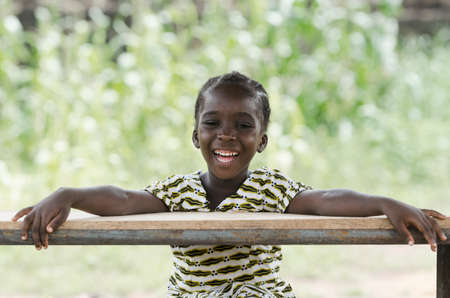 Little african girl sitting at wooden table and smiling at camera with blurred background Stock Photo
