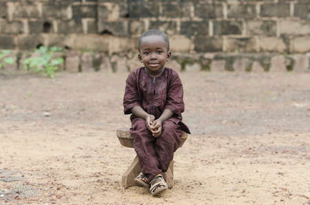 Little african boy sitting on wooden bench and looking at camera with blurred background