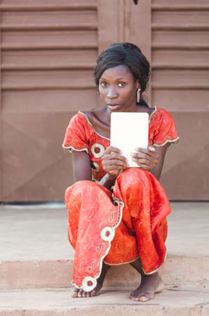 Young girl sitting on stone building and using tablet computer outdoors Stock Photo