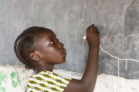Girl standing and writing on chalkboard in classroom