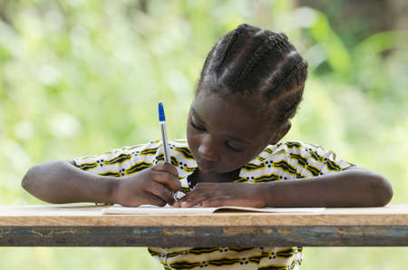 Young girl sitting at table and writing on paper with color pen Archivio Fotografico