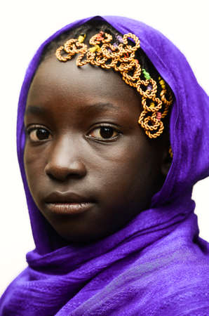 lybia: African child with violet African scarf on head, smiling lightly