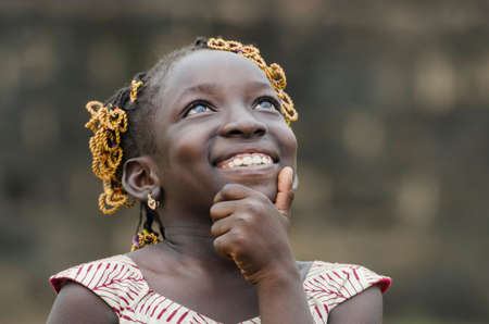 Young african girl with traditional accessories in hair looking at sky Archivio Fotografico