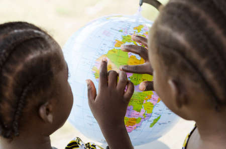 Rear view of two little african girls pointing fingers at globe