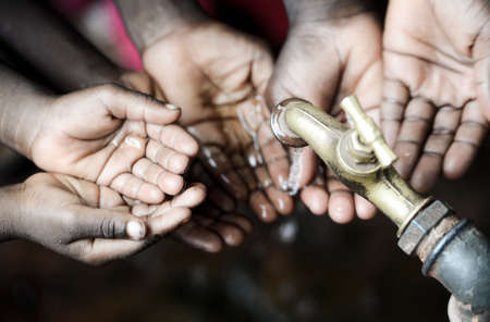 Lots of African children hold Their hands under a water pump