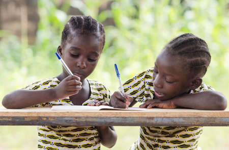 Young girls sitting at table and writing on paper with color pen