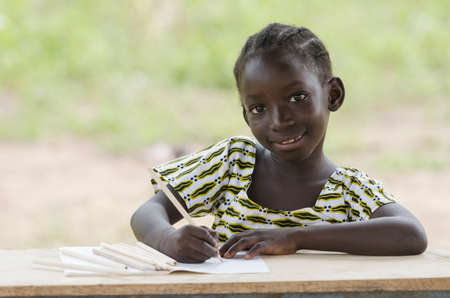 Beautiful African child sitting in her desk doing her homework at school