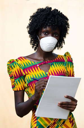Young woman in filtering half mask writing on paper and looking at camera
