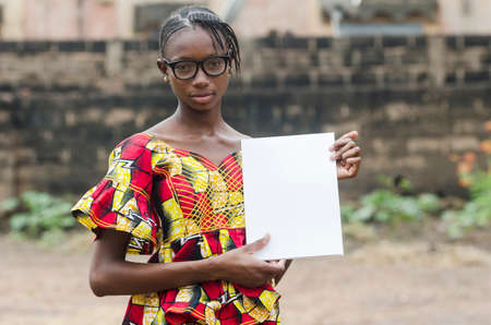 Young african girl in eyeglasses holding papers outdoors with blurred background