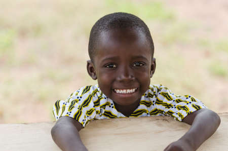 Little african boy sitting at wooden table and smiling at camera with blurred background Zdjęcie Seryjne