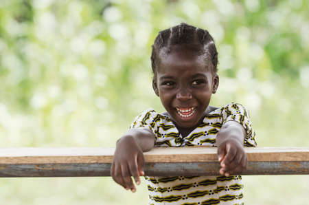 Little african girl sitting at wooden table and smiling at camera with blurred background Archivio Fotografico