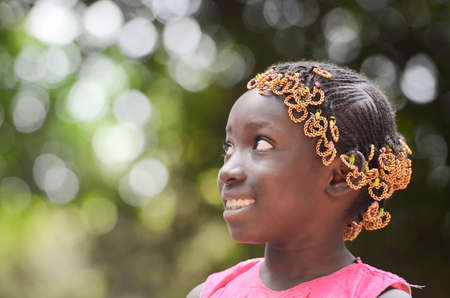 Side view portrait of young african girl with traditional accessories in hair with blurred background