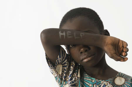 Little African boy asks for help by covering his face with his arm, isolated on white Archivio Fotografico