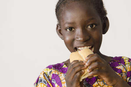 Young African girl eating some bread - isolated on white Zdjęcie Seryjne