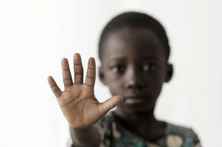 African boy makes a stop sign with his hand, isolated on white Zdjęcie Seryjne