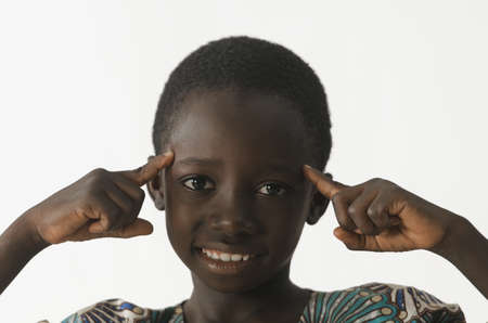 African ethnicity boy thinking with his fingers pointing to his head, isolated on white