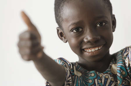 Handsome young African boy showing his thumbs up as a success symbol, isolated on white