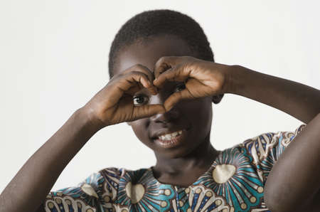 Little African black child showing heart symbol with his hands, isolated on white Zdjęcie Seryjne