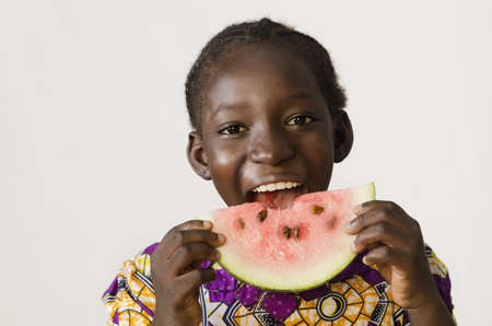 Young African girl eating some watermelon, isolated on white Zdjęcie Seryjne