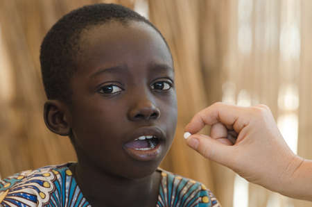 White doctor giving a pill to a little black African boy 写真素材
