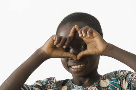Little African boy making a hand gesture while smiling, isolated on white