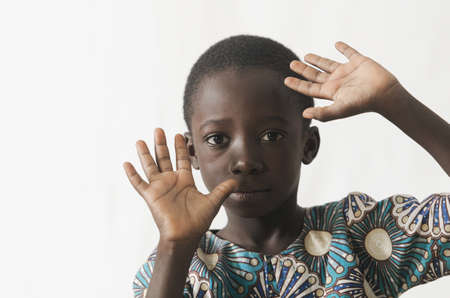 African child protecting his face with his hands, isolated on white