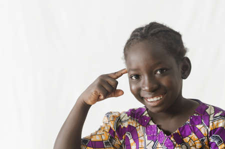 Gorgeous African girl pointing finger at her head, isolated on white Zdjęcie Seryjne