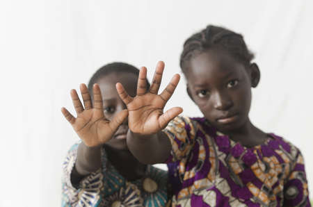 Two African children making stop sign with their hands, isolated on white