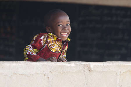 Handsome African Baby Boy Laughing Behind Wall at School Zdjęcie Seryjne - 102162422